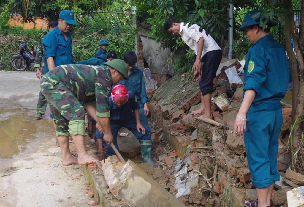 Cán bộ, chiến sỹ LLVT huyện Tuần Giáo giúp đỡ các gia đình khắc phục hậu quả mưa lũ.