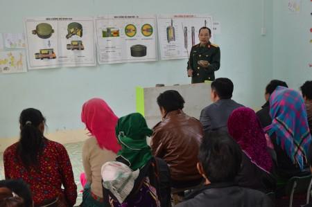 Ban CHQS huyện Yên Minh tuyên truyền cho nhân dân trên về tác hại của bom, mìn.