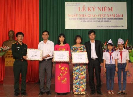 Thiếu tá Phạm Minh Trung và đại diện Công ty TNHH Dệt may tỉnh Nam Định trao 600 chiếc áo tặng học sinh Trường THCS Kim Đức.