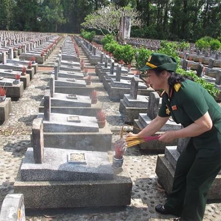 Cựu chiến binh Đặng Thị Hoathắp hương co đồng đội tại Nghĩa trang Liệt sĩ quốc gia Trường Sơn. Ảnh: qdnd.vn