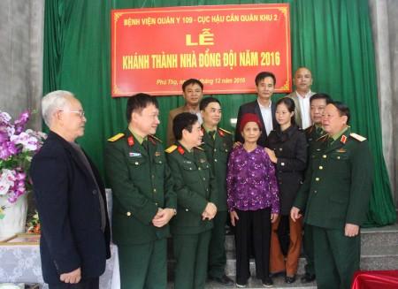 Thiếu tướng Vũ Sơn Hoàng, Phó Chủ nhiệm Chính trị Quân khu cùng các đại biểu dự lễ bàn giao nhà đồng đội chia vui với gia đình Trung úy QNCN Nguyễn Văn Tỉnh.