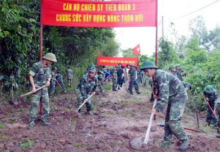 Bộ đội Lữ đoàn Phòng không 77 (Quân khu 7) giúp địa phương làm đường nông thôn mới. Ảnh: HOÀNG NAM